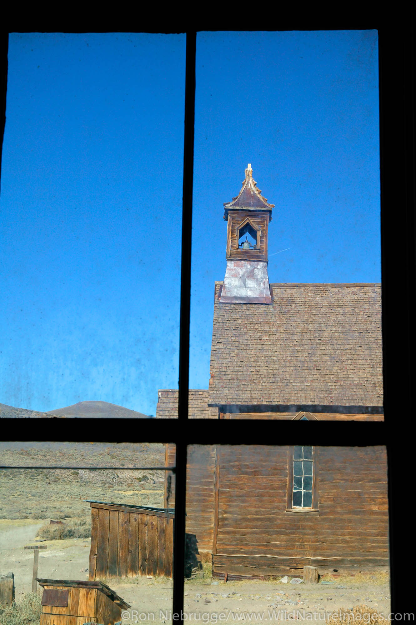 The old Methodist Church as viewed through the window of the Miller House, in the historic ghost town of Bodie.  Bodie was once...