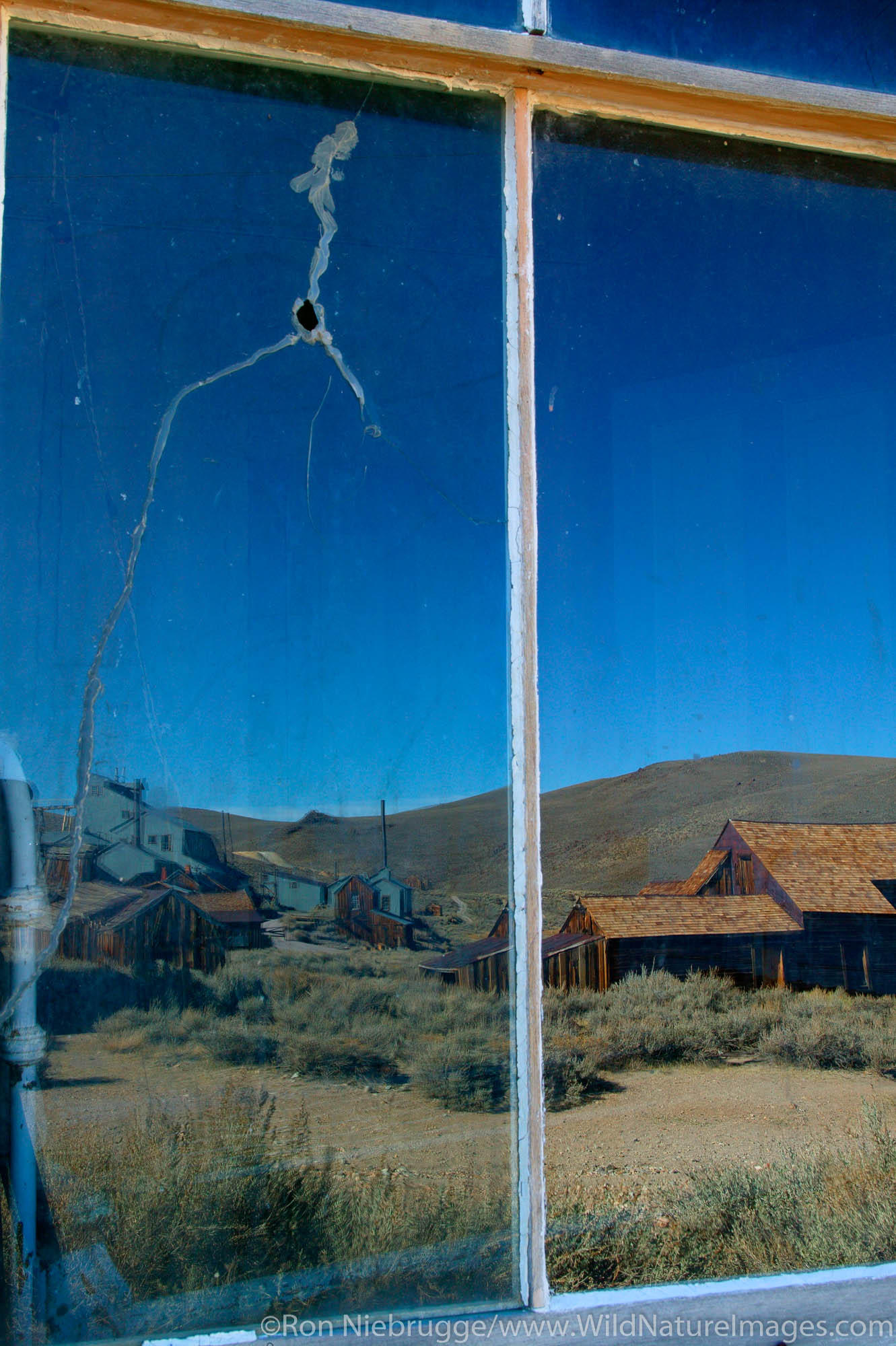 Reflections in the windows of one of the homes in the historic ghost town of Bodie.  Bodie was once bustling gold mining town...