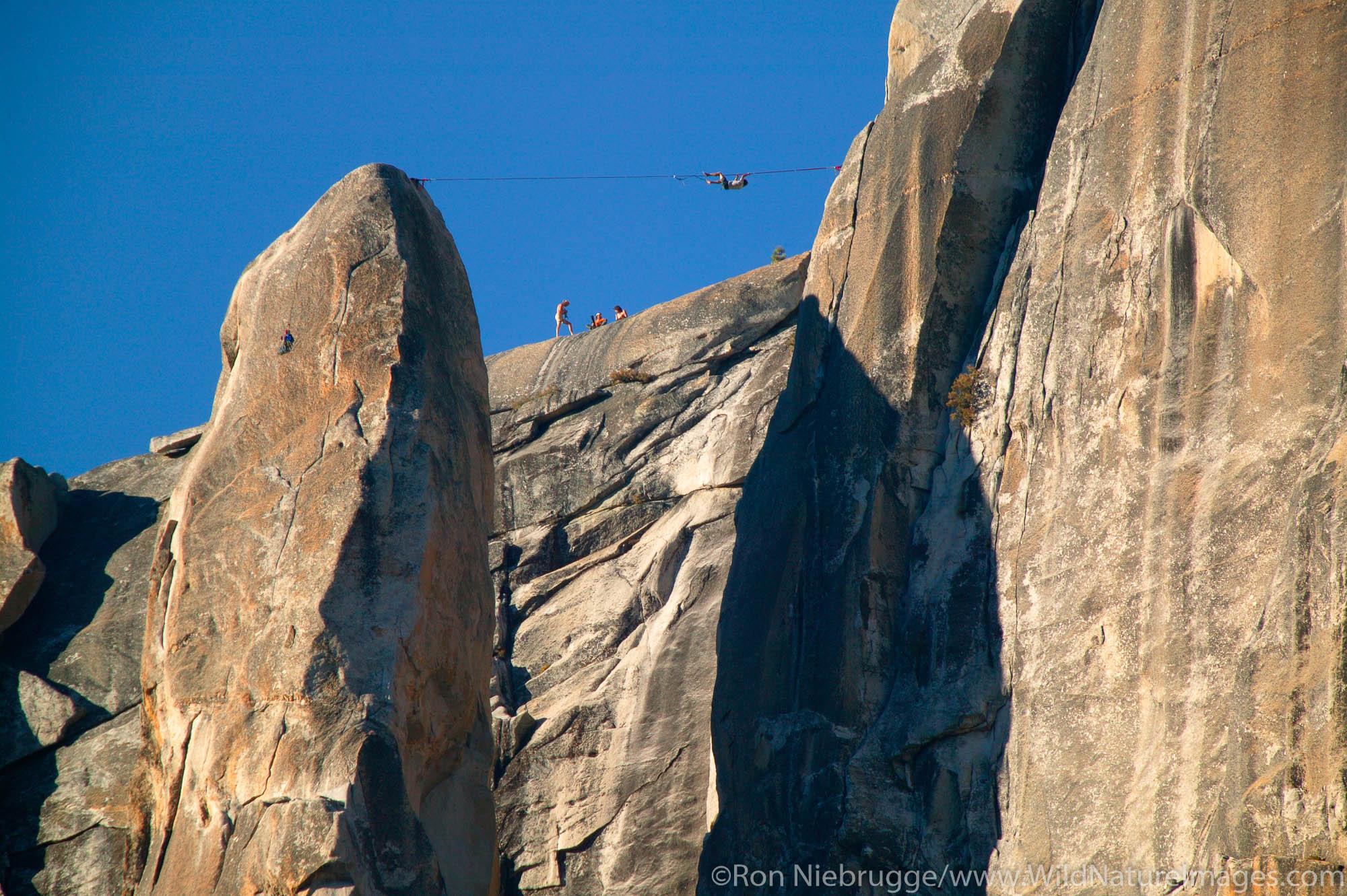 Climbers executing a tyrolean traverse  high above Yosemite Valley, Yosemite National Park, California.