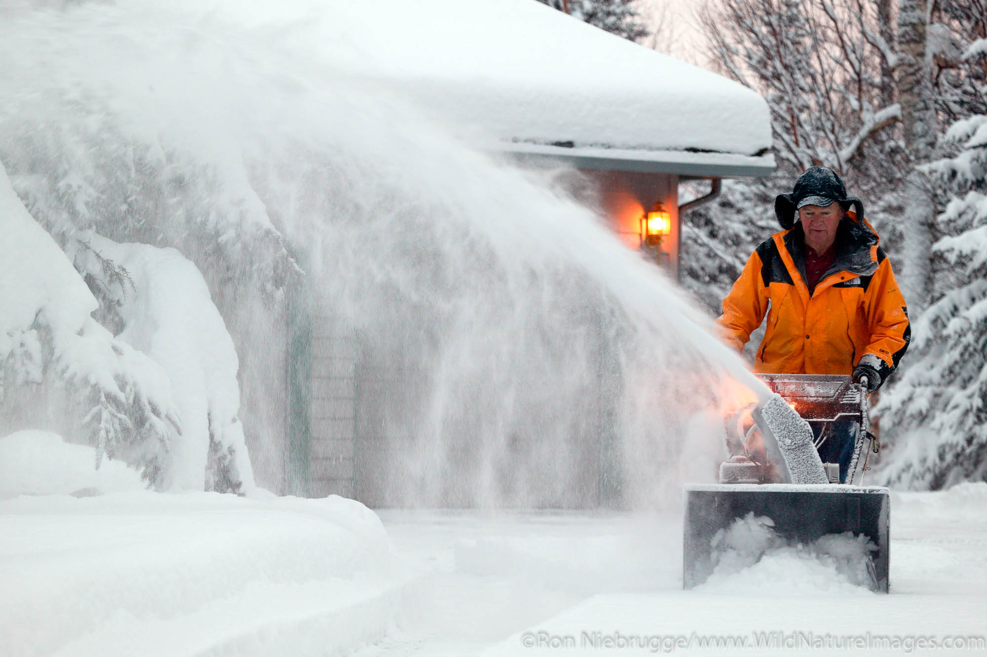 Man snowblowing his driveway after fresh winter snowstorm.   (Model  & Property Released)