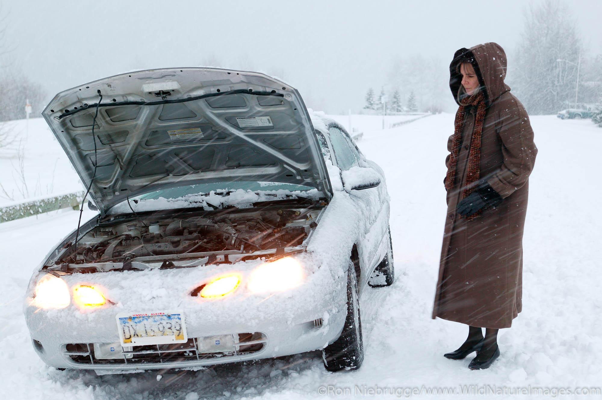 A female traveler with a disabled car during a winter snowstorm, Seward, Alaska.  (MR, PR)
