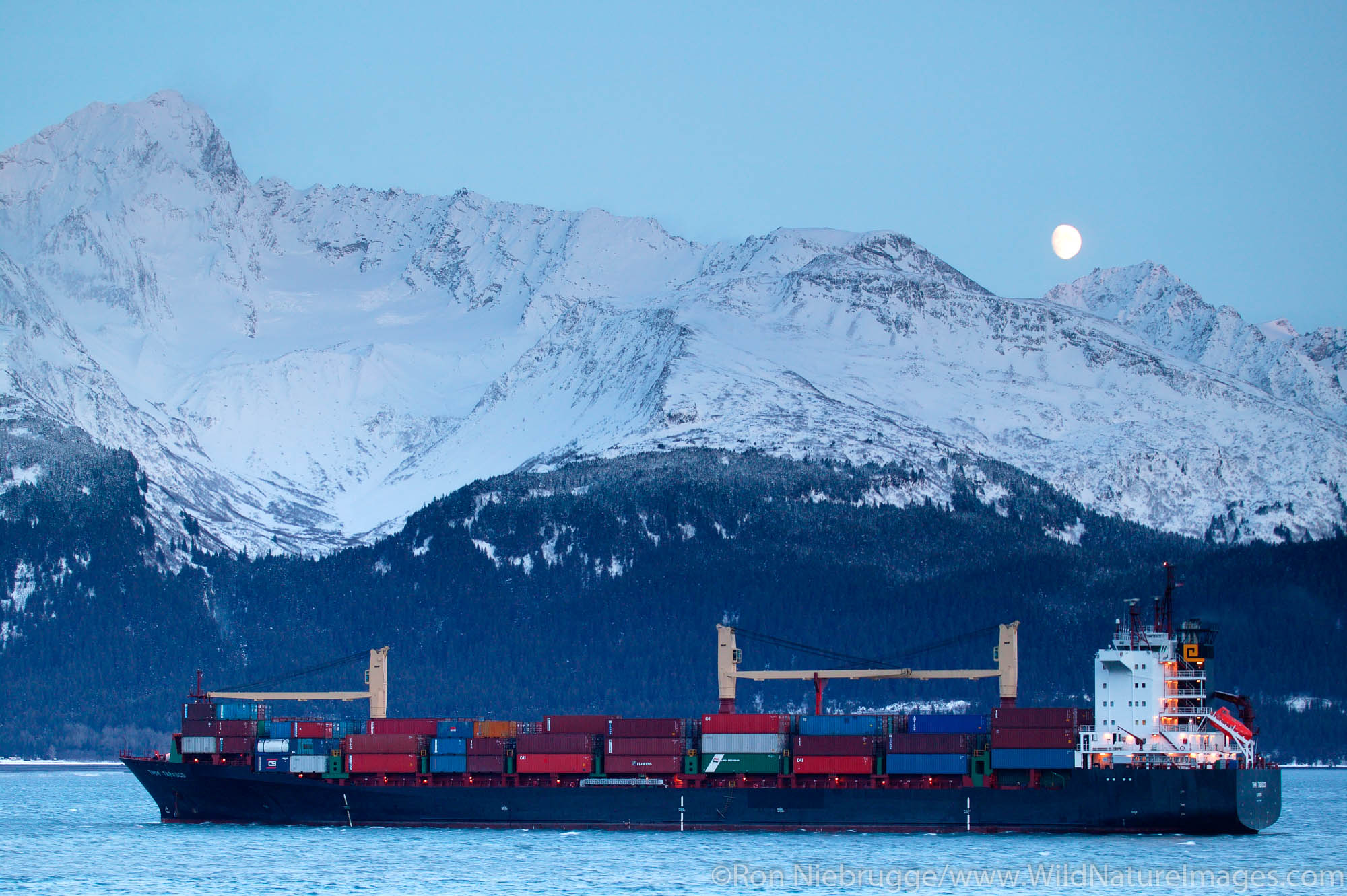The United Kingdom flagged container ship TMM Tabasco in Resurrection Bay under a full moon and in front of Mount Alice and the...