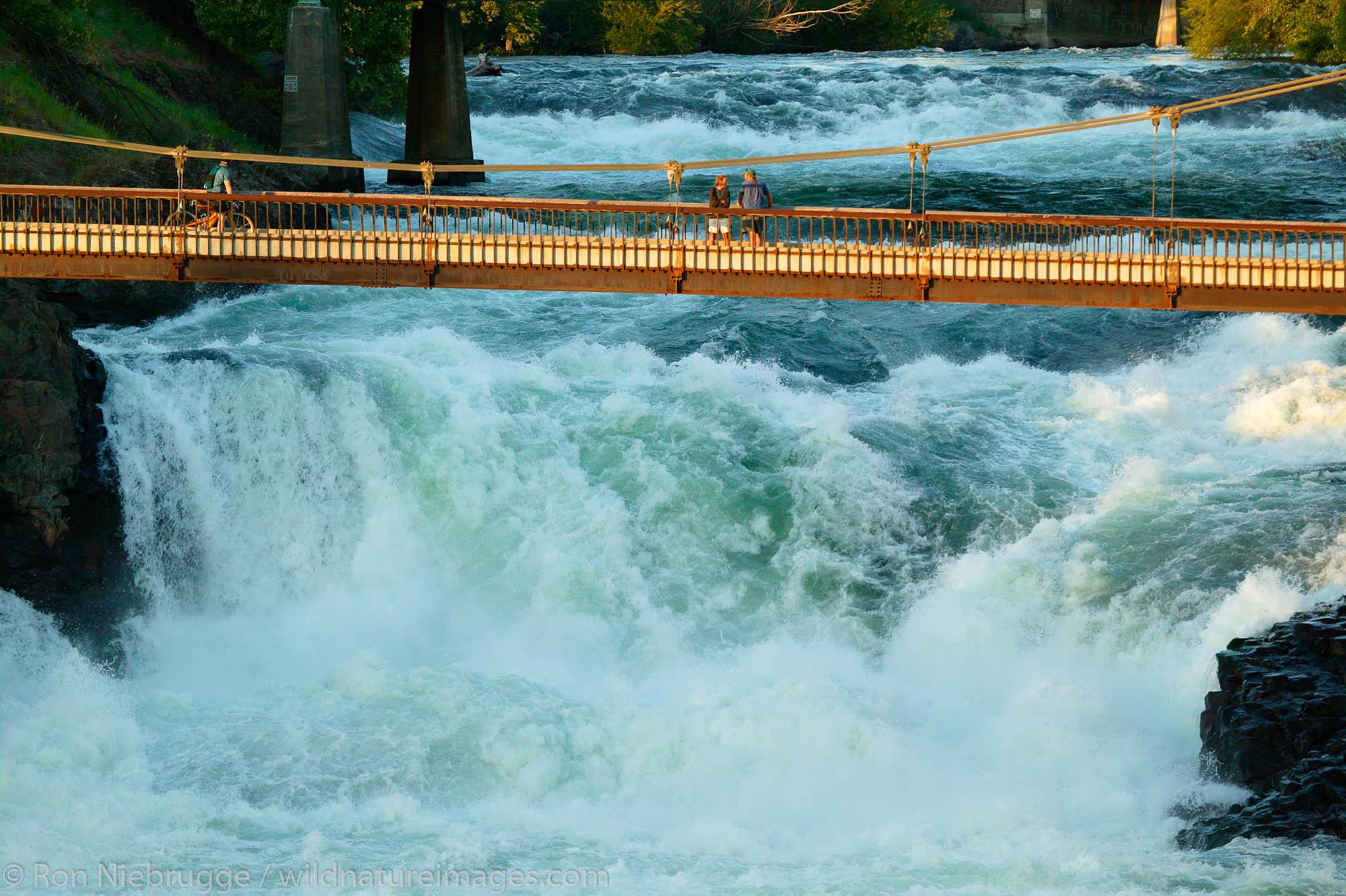 A bridge over the waterfalls along the Spokane River and Riverfront Park, downtown Spokane, Washington.  Riverfront Park was...