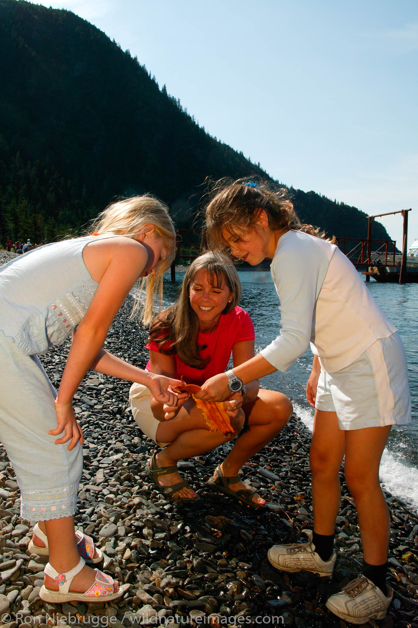 Janine Niebrugge (red) Jessica Wright (blue top) and Savannah Woolston (white top) on the beach of Kenai Fjords Tours property...