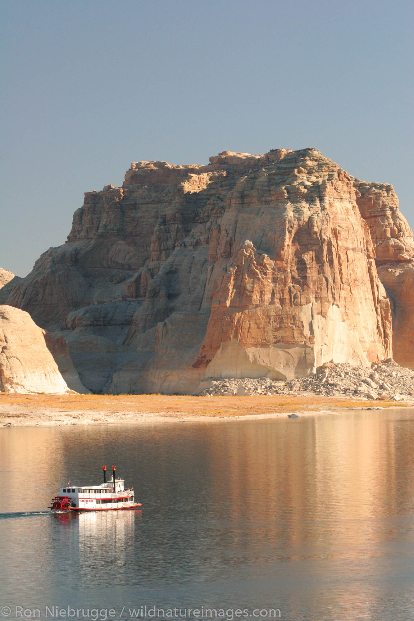 A tour boat passes by the Lone Rock Campground, Lake Powell and the Glenn Canyon Recreation Area, Utah.  This is near Page, Arizona...