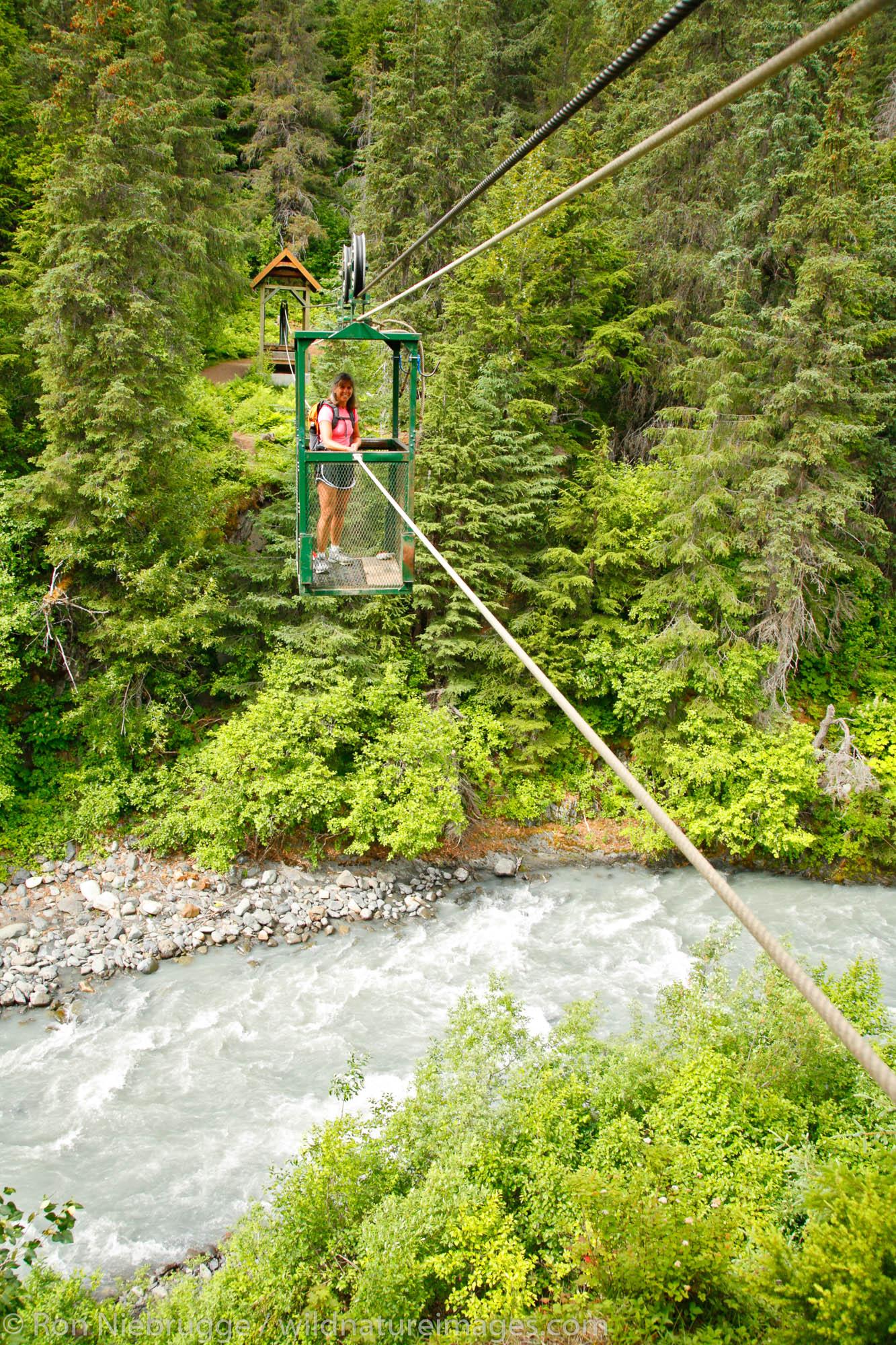 A hiker pulls herself across Glacier Creek on the aerial hand tram, Winner Creek Gorge Trail, Girdwood, Chugach National Forest...