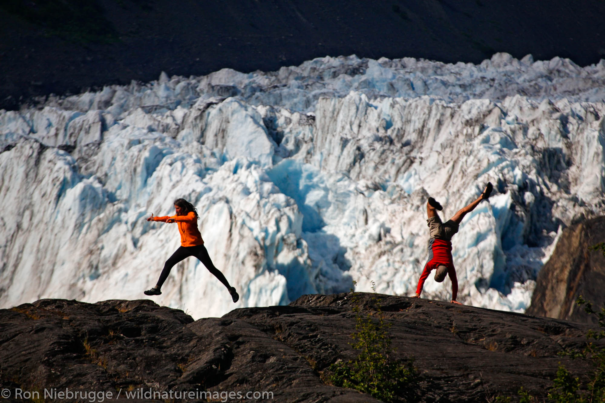 Hikers playing in front of Barry Glacier, Harrimon Fiord, Prince William Sound, Chugach National Forest, Alaska. (MR)