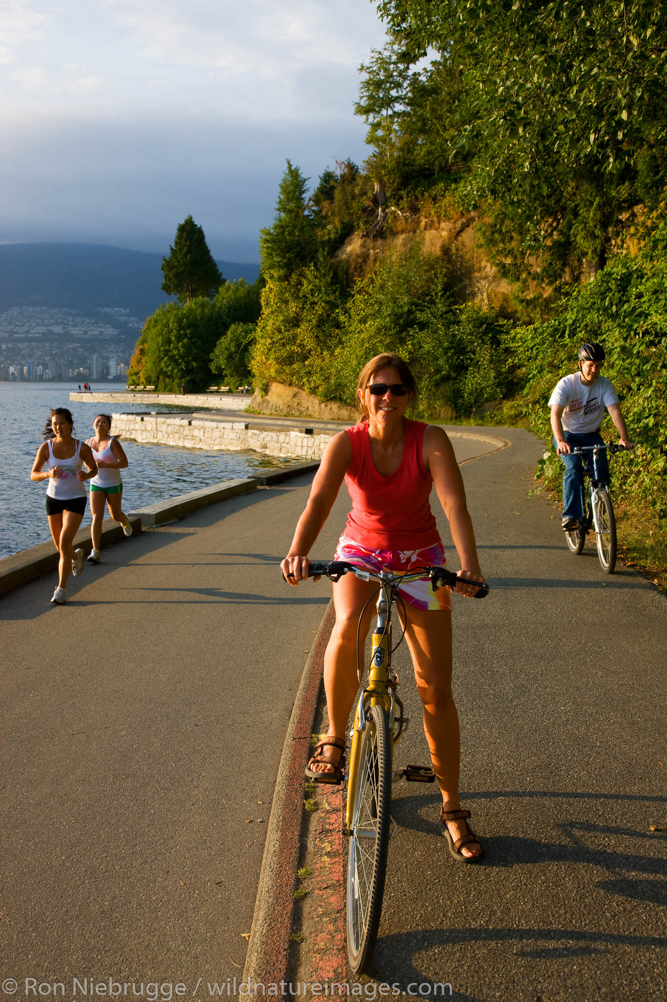 Bike riding on the coastal trail in Stanley Park, Vancouver, British Columbia, Canada.  (model released)
