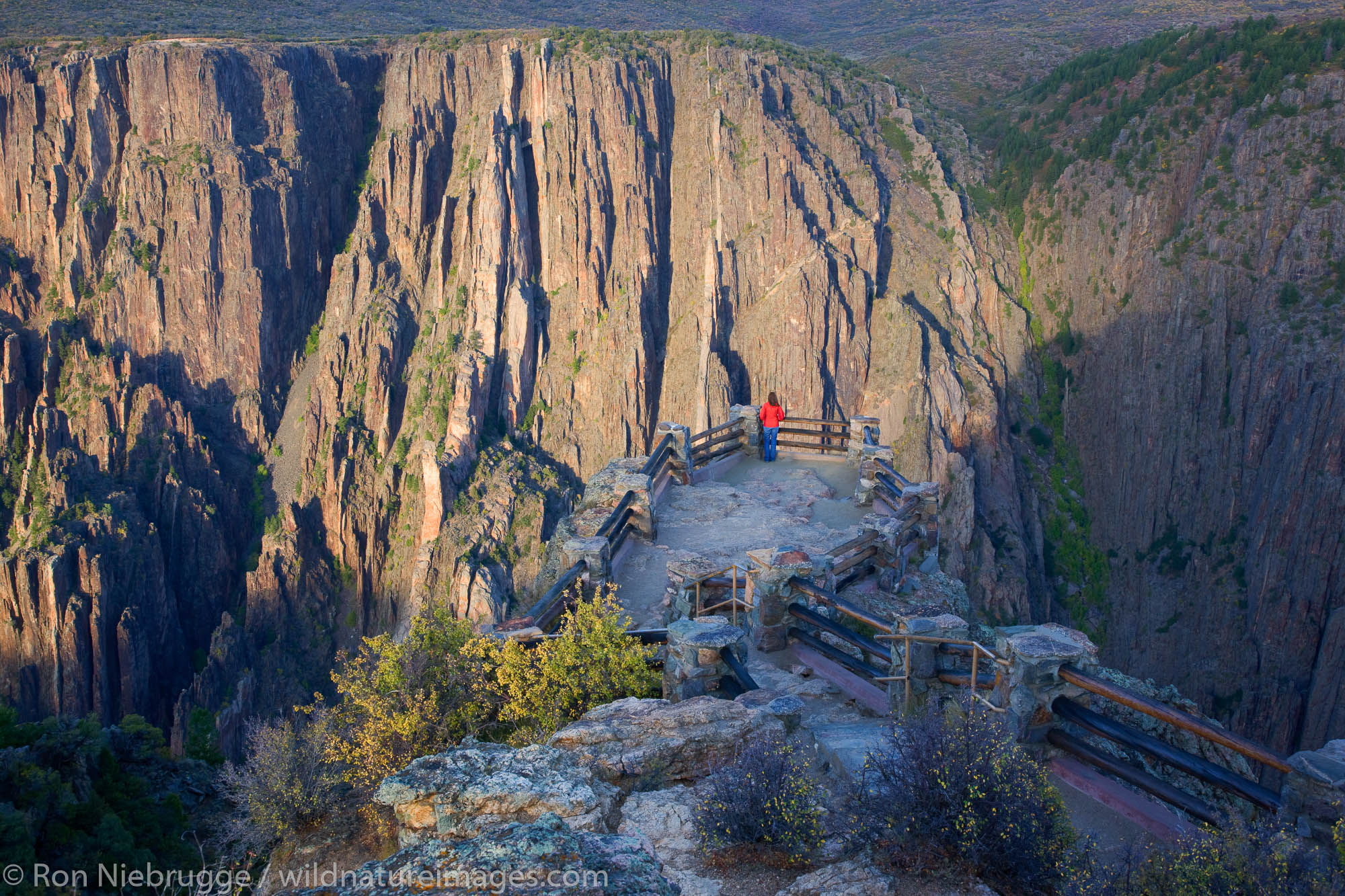 A hiker enjoys the viewpoint at Gunnison Point, Black Canyon of the Gunnison National Park, Colorado.  (model released)