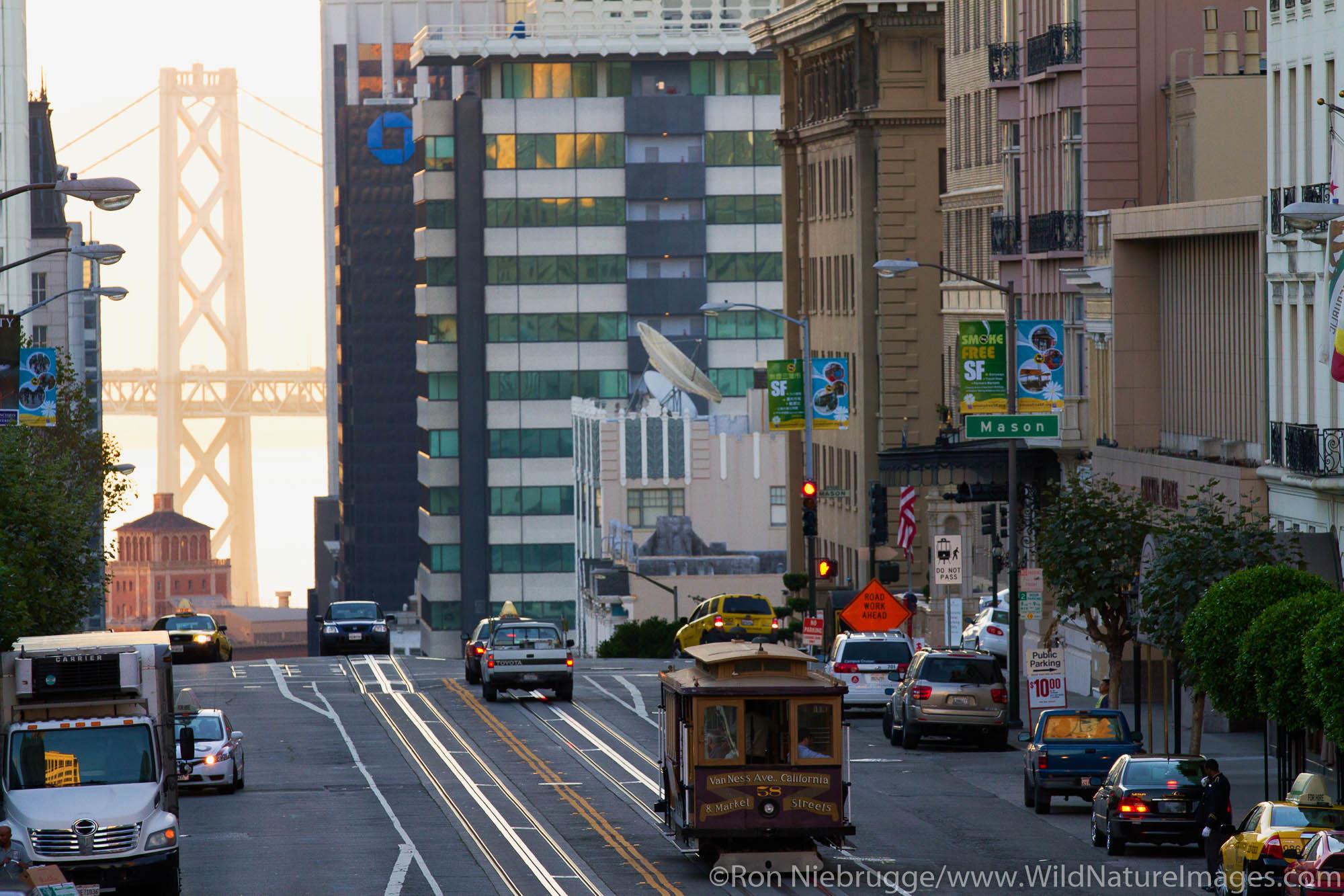 Cable Car makes its way through morning traffic, Bay Bridge in background.  San Francisco, CA