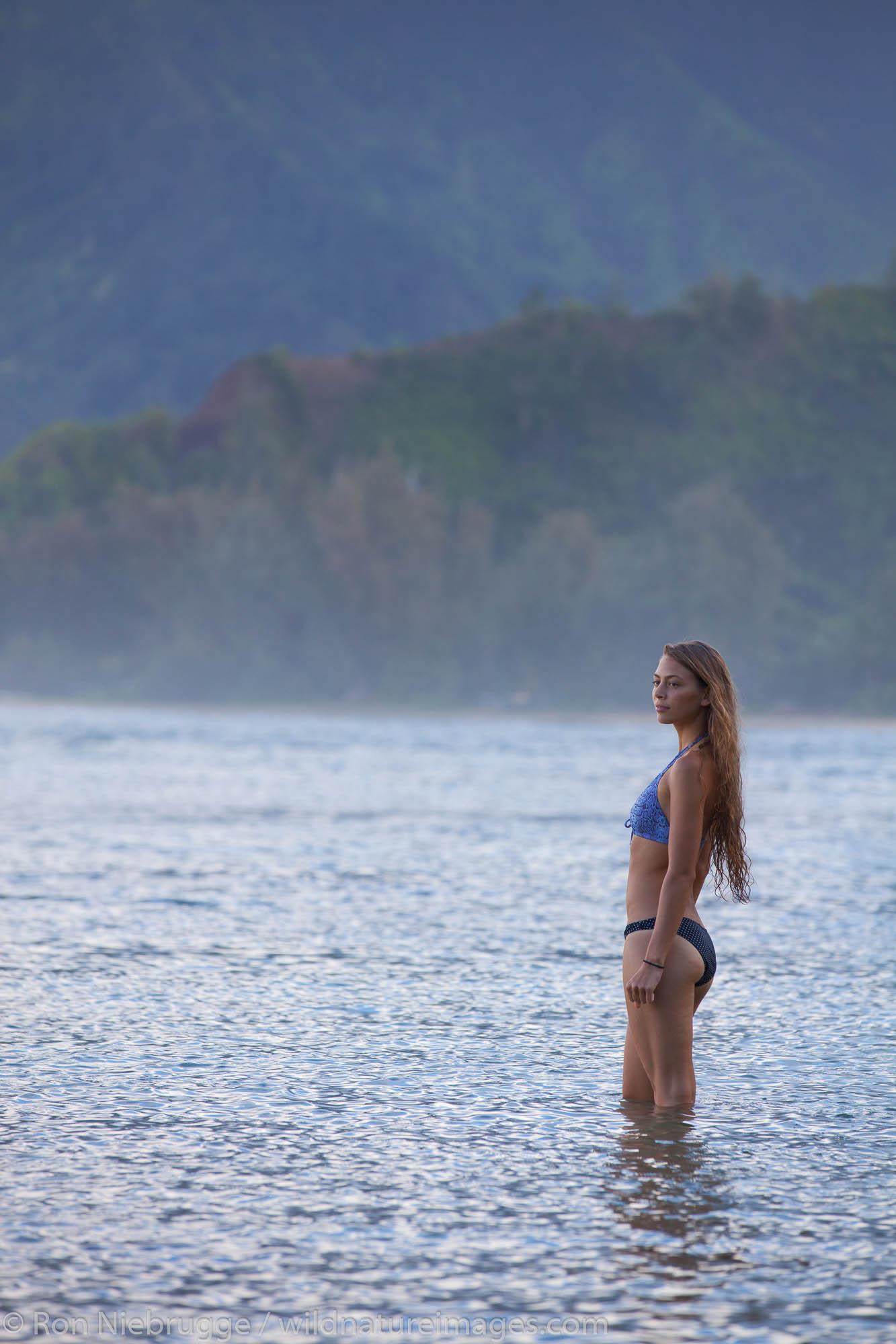 A young lady enjoying Hanalei Bay, Kauai, Hawaii.