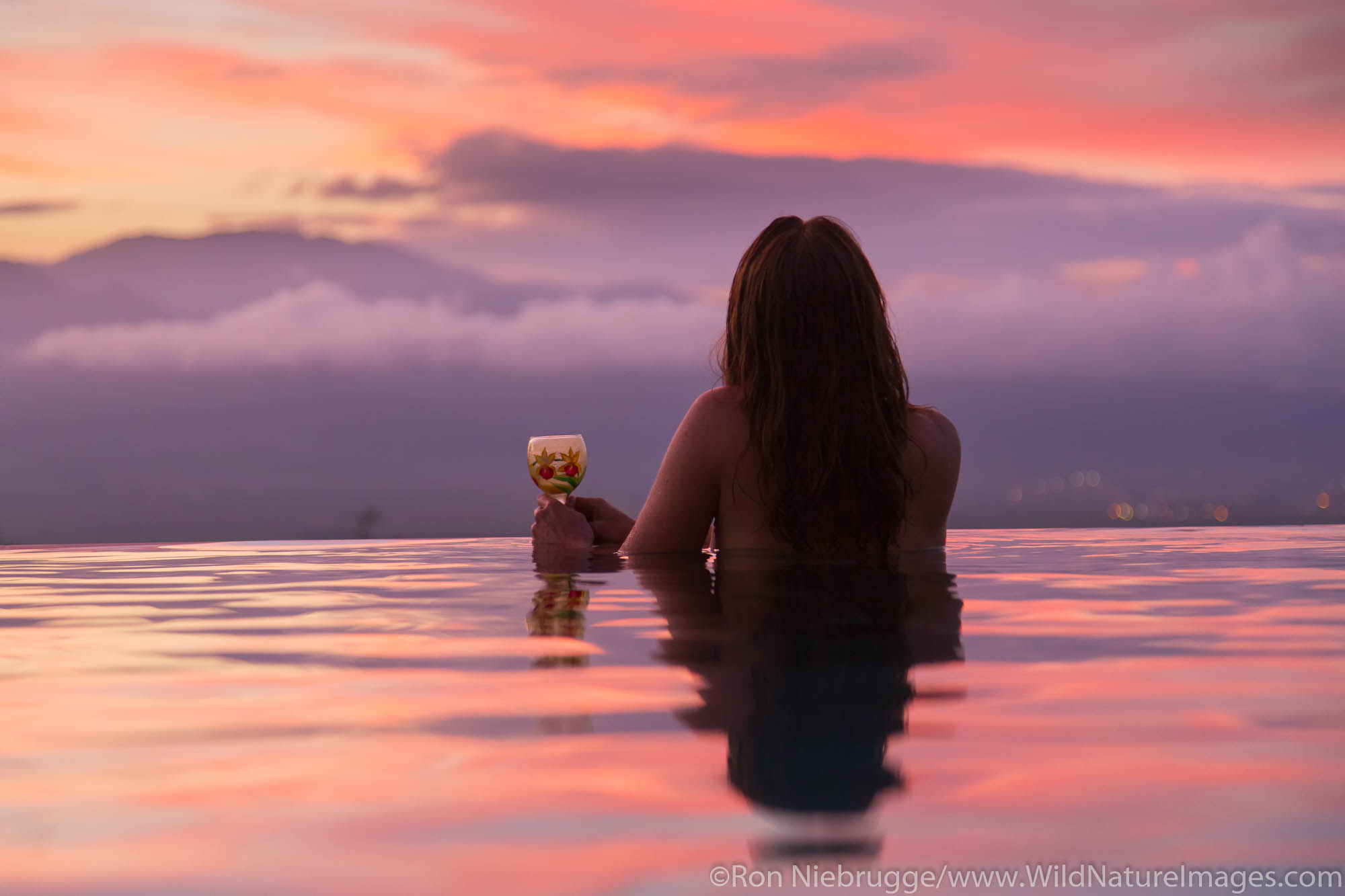 A visitor enjoying sunset from an infinitely pool, Maui, Hawaii.  (model released)