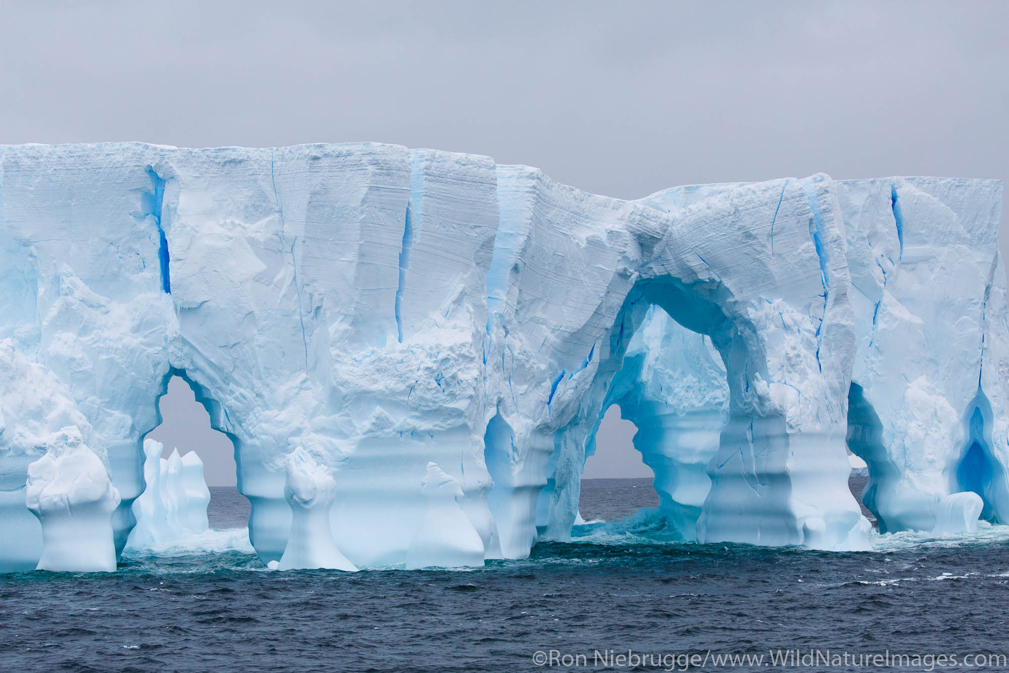 Huge arched iceberg south of the Antarctica Circle, Antarctica.