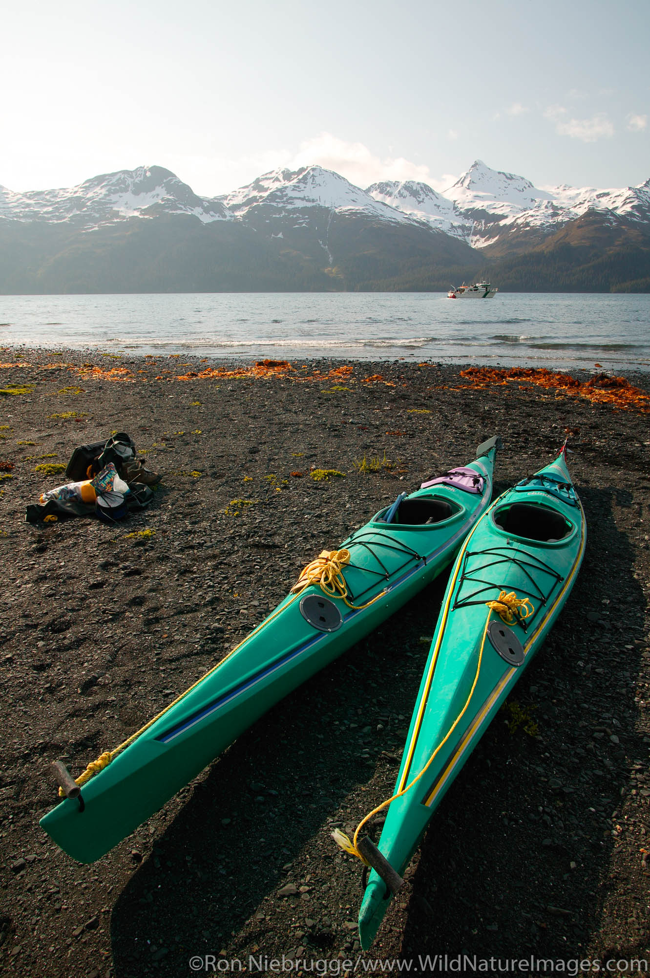 Kayaks on the beach in front of the North Arm public use cabin, Nuka Bay, with the Park Service boat Serac, Kenai Fjords National...