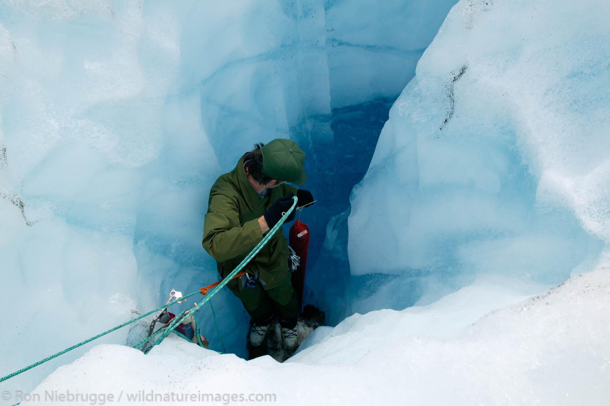 Park Service Resource Management Specialist Mike Tetreau positioning a transmitter used to measure glacier movement into a moulin...