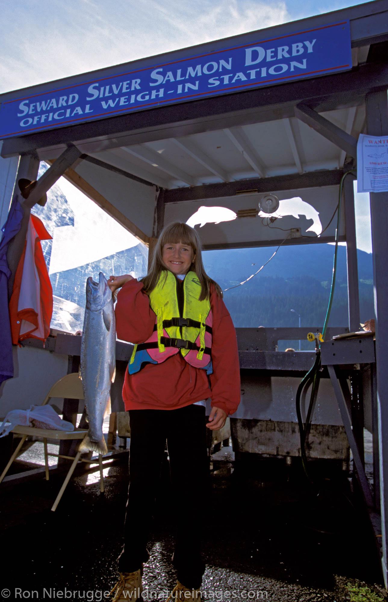 Young girl weighs in fish at Seward Silver Salmon Derby Booth.  Seward, Kenai Peninsula, Alaska.  MR