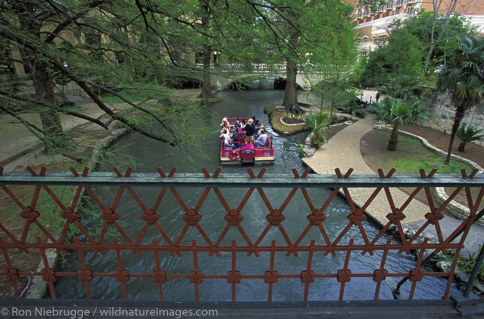A tour boat travels under a Iron Bridge over the Riverwalk, San Antonio, Texas.