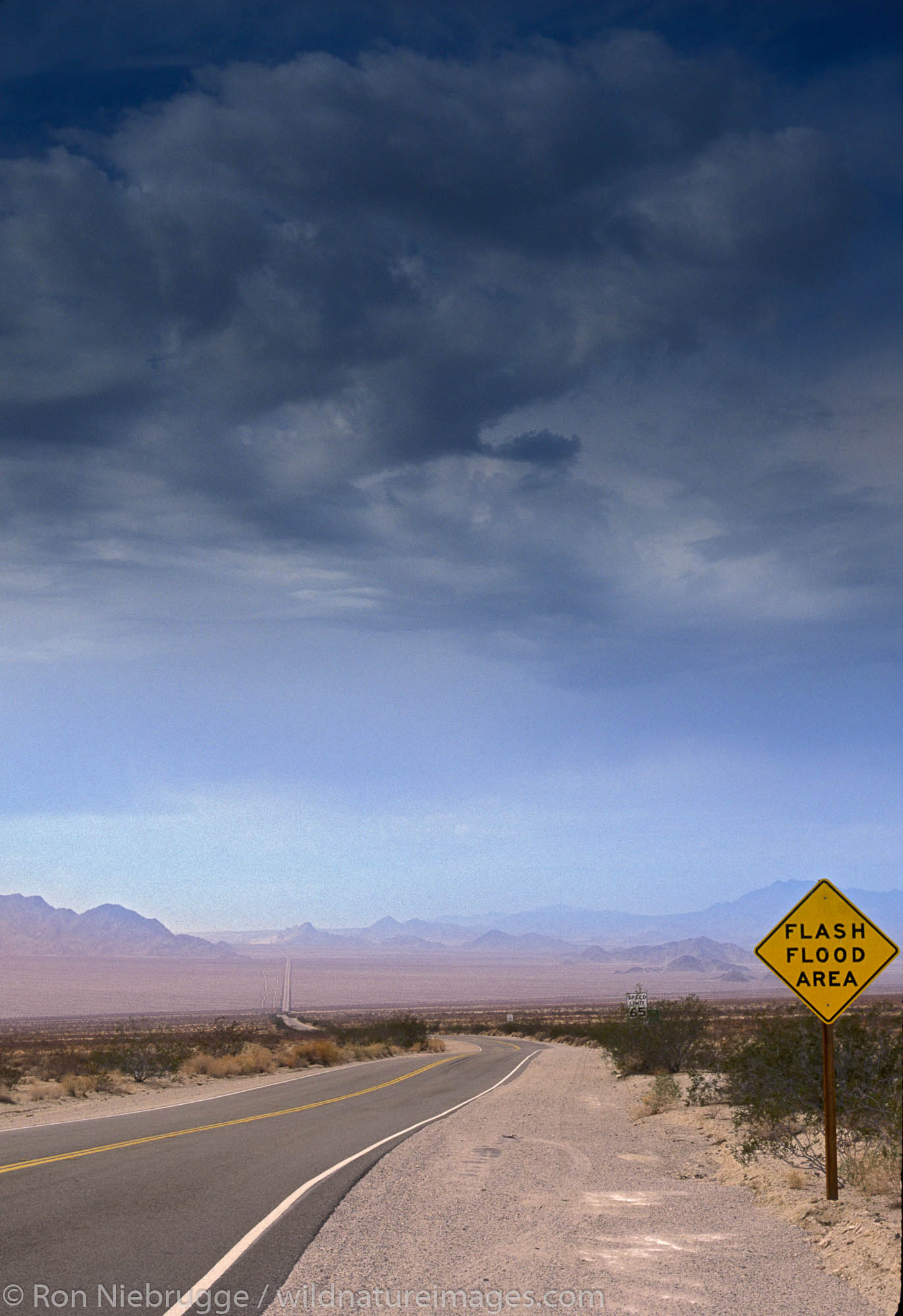 Flash flood warning signs during stormy weather on Highway 62, Mojave Desert, California.